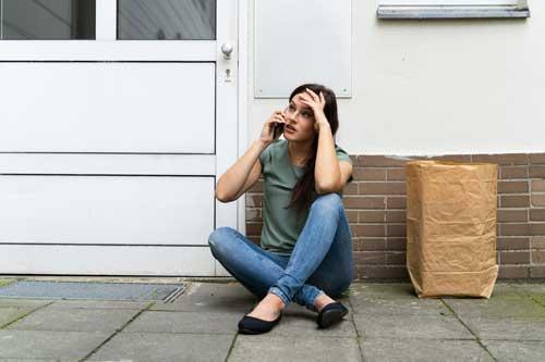 Femme au téléphone bloquer devant sa porte d'entrée