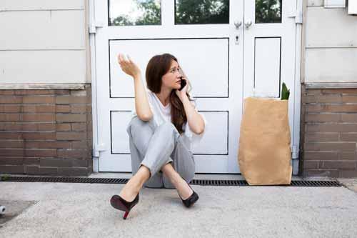 Femme assise au téléphone devant sa porte claquée