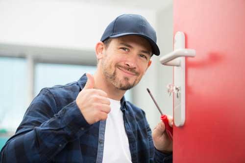Serrurier souriant avec le pousse levé venant d'ouvrir une porte claquée