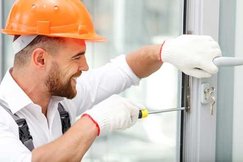 Serrurier souriant en train de réparer une serrure défectueuse