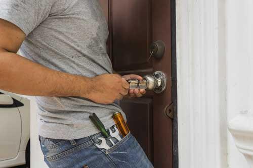 Artisan serrurier vérifiant l'ouverture d'une porte et le fonctionement de la serrure