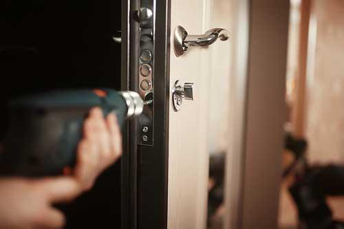 Perceuse en fonctionnement durant la réparation d'un porte blindée