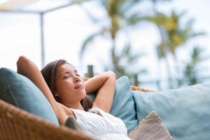 Femme se détend assise sur un canapé à l'exterieur en été
